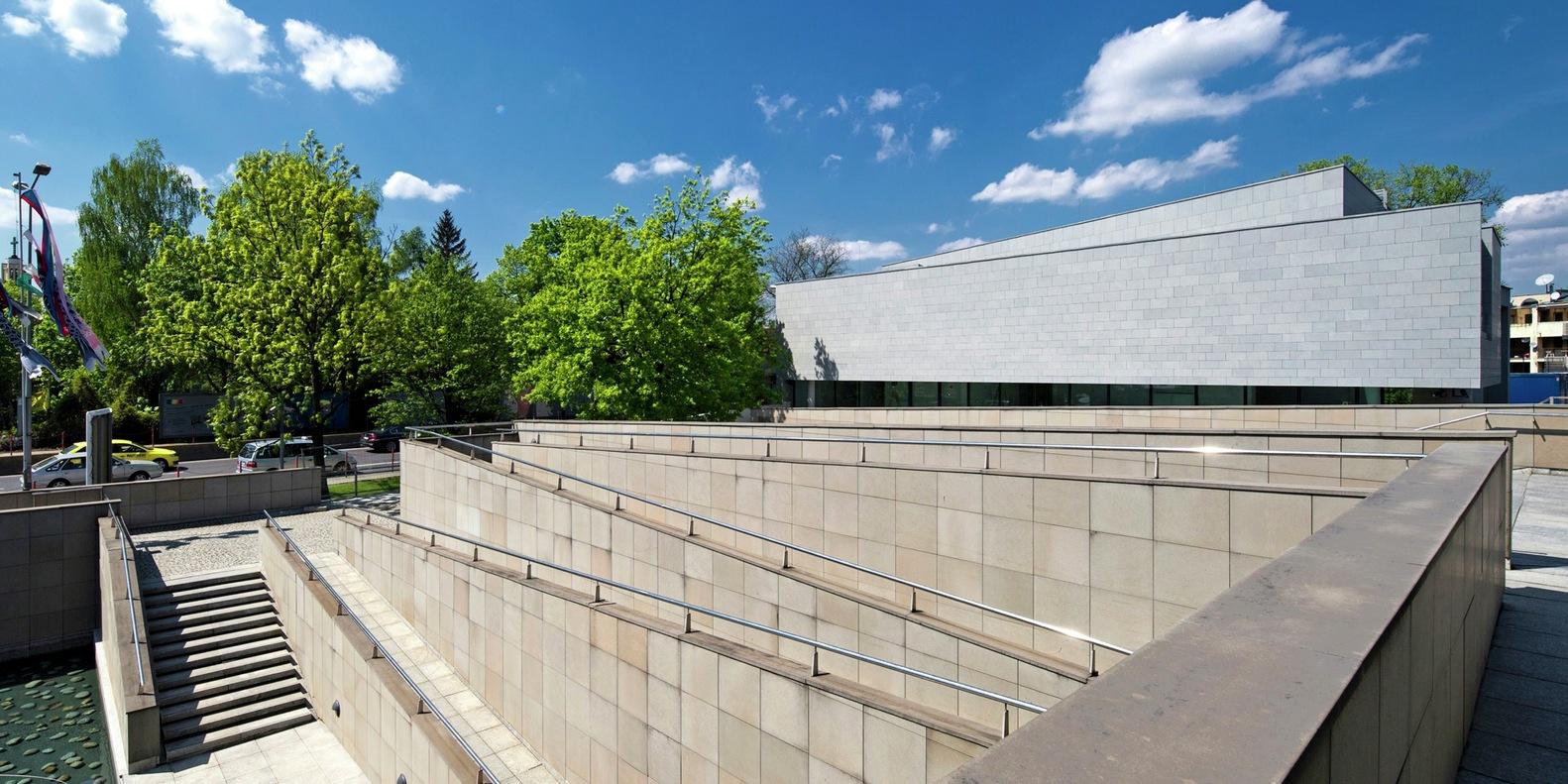 建筑形式 Manggha博物馆的屋顶是基于几何双曲面的几个并列水平抛物线的特殊形式,整个建筑体量比较完整。任何想要补充或扩展原有组合的动作无疑会打破现有的和谐。新的建筑应该努力贴近旧建筑,就我而言,应该尊重并突出主体建筑的独特性,创造一个合理的建筑背景,对外部环境进行补充和引导。 因此,Manggha博物馆在形式和功能上仍处于主导地位,在规模和组合上处于次要地位。新建筑的外形尽可能得远离Manggha博物馆的主入口和基地,以免挡住ul.